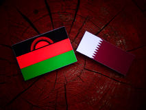 Malawi flag with Qatari flag on a tree stump isolated. Malawi flag with Qatari flag on a tree stump Stock Photos