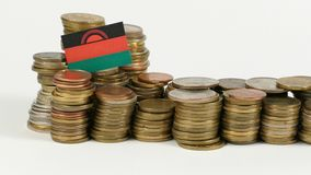 Malawi flag with stack of money coins. Malawi flag waving with stack of money coins stock video
