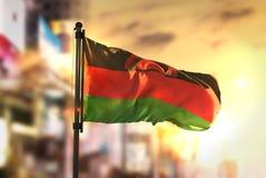 Malawi-Flagge gegen Stadt unscharfen Hintergrund an der Sonnenaufgang-Hintergrundbeleuchtung Stockfotografie