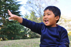 A Malay child with a hand raised up. A child poses with one hand raised up while sitting on a grass lawn Royalty Free Stock Image