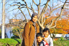 A Malay family posing for the camera in autumn. The portrait of a mother bonding with her son and daughter by the site of trees in fall season Stock Photography