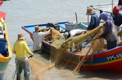 Malay fishermen cleaning a net Royalty Free Stock Photography