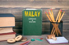Malay language and culture concept. Book on a wooden background stock images