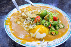 Malay Mee Rebus Dish. Malay Mee Rebus Noodle Dish Garnished with Cut Chili Peppers Tofu Chinese Celery and Hard Boiled Egg stock photography