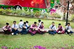 Malay muslim children have a lunch on a grass in Kuala Lumpur, M. KUALA LUMPUR, MALAYSIA - 31 OCT 2014: Malay muslim children have a lunch on a green grass lawn Stock Photo