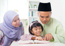 Malay Muslim parents teaching child Stock Photos