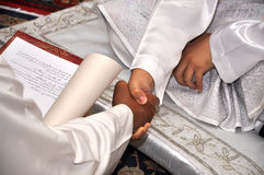 Malay traditional wedding ceremony. Shake hand to accept vow Stock Image