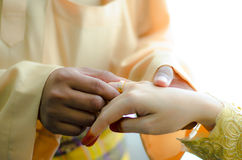 Malay wedding ceremony, Malaysia. Groom putting a diamond ring to his bride's finger Stock Photography
