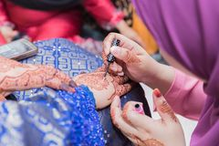 Malay Wedding Henna. The henna tattooist assisting the bride in the touch up of her wedding henna and installing additional blings stock images