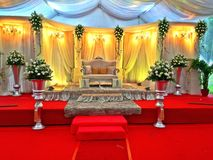 Malay wedding stage decor -Singapore. A lavishly decorated stage with a throne-like sofa and cushions for the bride and bridegroom to sit on stock photos