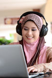 Malay woman. Young pretty Asian muslim woman in head scarf listens to audio with headphone while working on laptop in cafe Royalty Free Stock Photography
