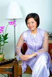 Malay woman in purple lace dress and long skirt stock photo