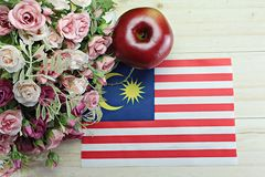 Malaysia flag, apple and flower on wood background Stock Image
