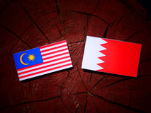 Malaysia flag with Bahraini flag on a tree stump isolated. Malaysia flag with Bahraini flag on a tree stump Stock Images