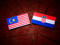Malaysia flag with Croatian flag on a tree stump  Royalty Free Stock Photography