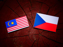 Malaysia flag with Czech flag on a tree stump  Royalty Free Stock Images