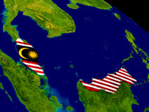 Malaysia with flag on Earth Royalty Free Stock Photo