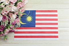 Malaysia flag and flower on wood background Stock Photo