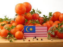 Malaysia flag on a wooden panel with tomatoes isolated on a whit Stock Photo