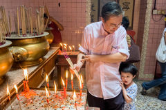 Malaysia, in Kuala Lumpur during Chinese new year in the Sin Sze Si Ya Temple. A father initiates his daughter to honor the gods royalty free stock photo
