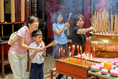Malaysia, in Kuala Lumpur during Chinese new year in the Sin Sze Si Ya Temple. A mother shows her son how to honor the gods stock photo