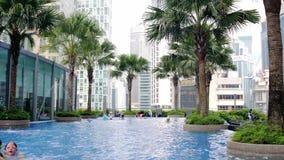 Malaysia, Kuala Lumpur, am 7. Juli 2018 Swimmingpool auf dem Dachgeschoss des Hotels mit Stadtansichten Langsame Bewegung 3840x21 stock video footage