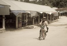 Poverty boys riding on a bicycle along a empty street royalty free stock images