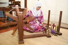 Malaysia National Craft Day 2011. KUALA LUMPUR, MALAYSIA - MARCH 4: Norlianawati Ayob, a traditional Songket weaver prepare a yarn for the weaving process at the Stock Images