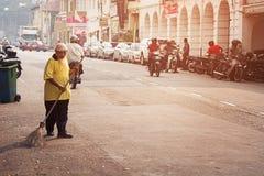 MALAYSIA, PENANG, GEORGETOWN - CIRCA IM JULI 2014: Fegen des alten Mannes Stockfoto