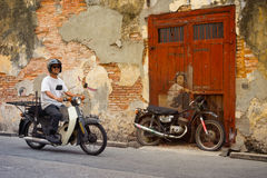 MALAYSIA, PENANG, GEORGETOWN - CIRCA JUL 2014: Man on a real mot Stock Photos