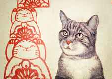 MALAYSIA, PENANG, GEORGETOWN - CIRCA JUL 2014: Mural with realis. Tic picture of a tortoiseshell cat beside red, stylized rendering of cats in a pattern Stock Illustration
