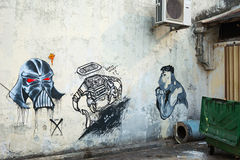 MALAYSIA, PENANG, GEORGETOWN - CIRCA JUL 2014: Three contemporary mural images from different artists, all on one cement wall. stock image