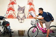 MALAYSIA, PENANG, GEORGETOWN - CIRCA JUL 2014: A tourist on a bi Stock Images