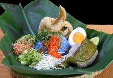Malaysia Popular Nasi Kerabu. The Blue Rice ( Nasi Kerabu ) accompanied with Salted Egg, Fish Crackers,Sliced Lemon Grass,Sliced Long Bean,Sliced White Cabbage Royalty Free Stock Image
