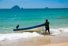 Malaysian beach and man struggling with his boat stock images