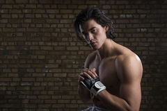 Malaysian boxer. Bare chested young Malaysian boxer wearing fingerless boxing gloves Stock Photo