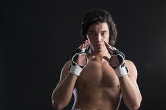 Malaysian boxer fighting. Bare chested young Malaysian boxer wearing fingerless boxing gloves Royalty Free Stock Photography