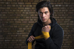 Malaysian boxer. Young Malaysian boxer wearing hoodie and wrapping straps around hands stock photography