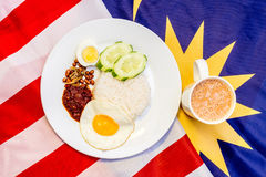 Malaysian Breakfast - Nasi Lemak and Teh Tarik on Malaysia Flag. Stock Photos
