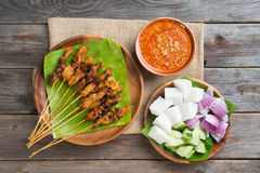 Malaysian chicken satay. Overhead view Malaysian chicken satay with delicious peanut sauce, ketupat, onion and cucumber on wooden dining table, one of famous royalty free stock photos