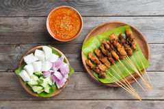 Malaysian chicken sate. Overhead view Malaysian chicken sate with delicious peanut sauce, ketupat, onion and cucumber on wooden dining table, one of famous local royalty free stock photography