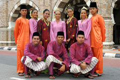 Malaysian cultural outfits. Traditional Malay attire is the baju melayu, a loose tunic which is worn over trousers and usually accompanied with a sampin, which Royalty Free Stock Images