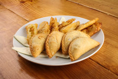 Malaysian curry puff. Delicious Malaysian curry puff and crispy fried banana served on white plate on wood background Stock Image