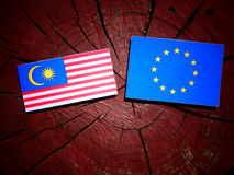 Malaysian flag with EU flag on a tree stump isolated. Malaysian flag with EU flag on a tree stump Stock Photos