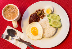 Malaysian Food - Nasi Lemak and Frothy Teh Tarik on a red backgr Royalty Free Stock Image