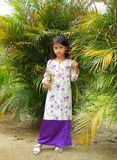 Malaysian Girl. A Malaysian girl wearing malay baju kurung standing by groups of palm trees Royalty Free Stock Image