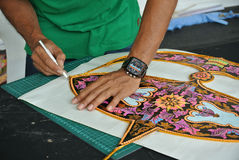 Malaysian kite maker working on a kite in his workshop Stock Photos