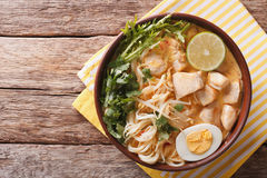 Malaysian laksa soup with chicken, egg, noodles and herbs close. Up in a bowl on the table. horizontal view from above Stock Photos