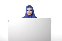 Malaysian malay woman. Malaysian asian malay woman holding an empty white board for content space isolated in white Stock Photo