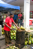 Malaysian man cutting young coconuts